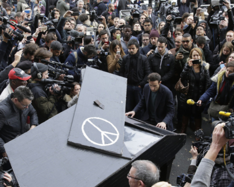A man plays piano near the cordened off area around the Bataclan theatre in the 11th district of Paris on November 14, 2015, after a series of attacks on the city resulting in the deaths of at least 120 individuals. More than a hundred people were gunned down at the Bataclan theatre in Paris late Friday during a concert by the US band Eagles of Death Metal. AFP PHOTO / KENZO TRIBOUILLARD