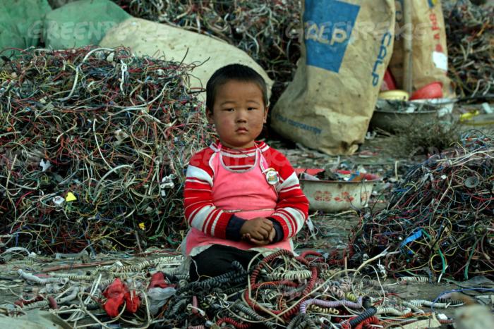 Un bambino in mezzo a una montagna di rifiuti elettronici a Guiyu (Fonte foto: media.greenpeac.org)