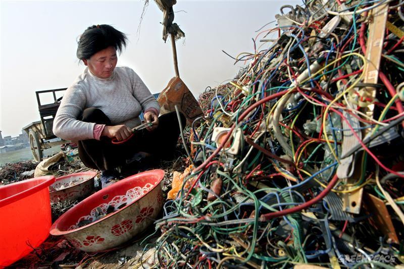 Una donna al lavoro nella discarica di rifiuti tecnologici - E-waste - più grande del mondo, a Guiyu, in Cina (Fonte foto: greenpeace.org)