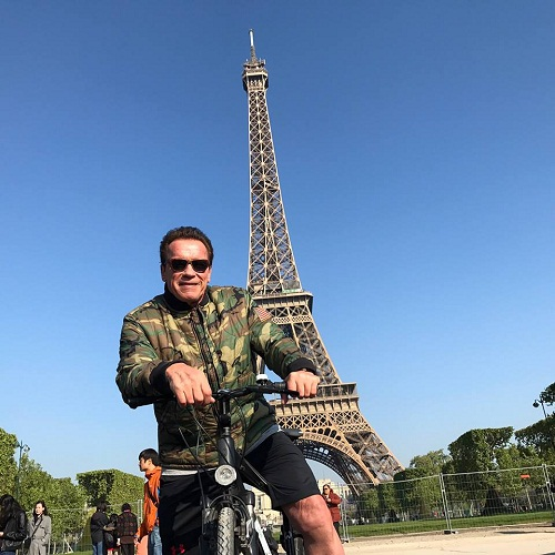 Arnold Schwarzenegger in giro in bicicletta per le strade di Parigi
