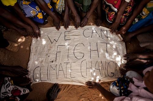 Medlemmer av drivhuset Kwoola Mathina Group, et lokalsamfunnsinitiativ for å lære seg klimatilpasningsmetoder, med en klar melding.