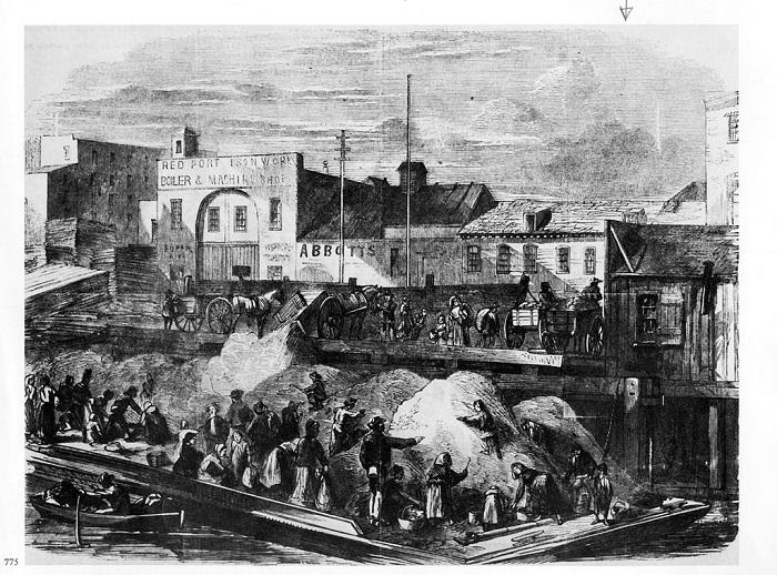 Gli straccivendoli rovistano tra i rifiuti ammucchiati nelle discariche pubbliche, in una città portuale inglese Foto: dizionaripiu.zanichelli.it