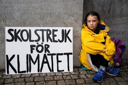Greta Thunberg in posa con il cartello che è il suo simbolo e il suo motto